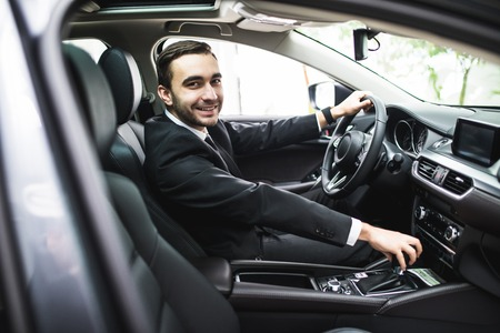 transport, business trip, destination and people concept - close up of young man in suit driving car