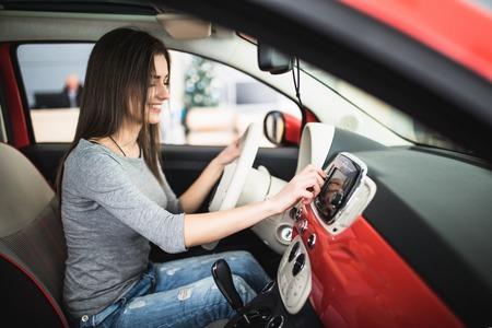 Car dashboard. Radio closeup. Woman sets up radio Foto de archivo