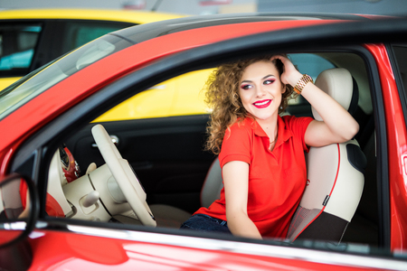 Young beautiful woman in her car smiling at camera.