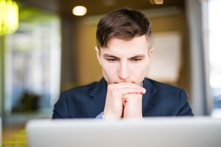 portrait of serious man looking at laptop in office