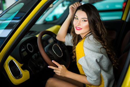 Beautiful Smiling woman driving car, attractive girl sitting in automobile.