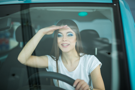 streight: Smiling woman driving car looking streight front Stock Photo