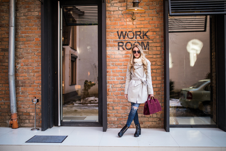 Young beautiful girl in stylish sunglasses and with a fashionable bag at work building Stockfoto