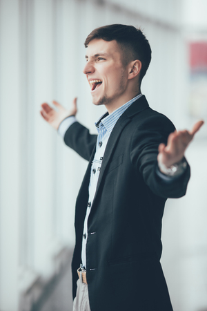 profesional: Business man with rised hands in his office Stock Photo