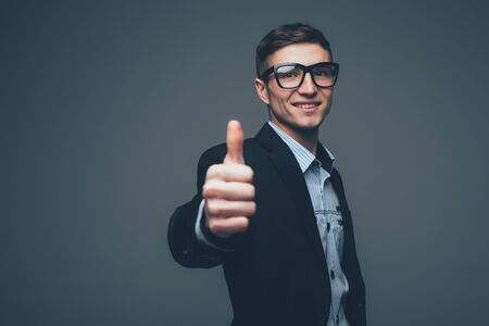 Grinning man in dark suit jacket with two thumbs up over gray background.