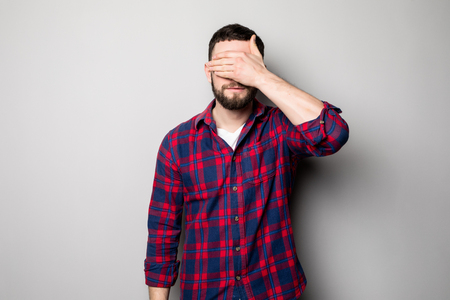 ignore: Portrait of a young casual man covering eyes with hand isolated on the gray background
