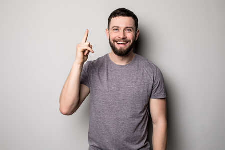Young smiling man having a good idea isolated on white. Copy space and plaid t shirt. Finger up. Selective focus.