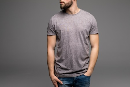 collarless: A man in a grey t-shirt and denims holds his hands in pockets. Isolated on grey