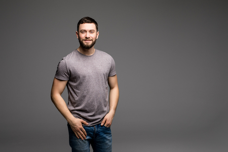 natural light: closeup portrait of a casual young man holding his hands in his pockets while looking into the camera. on gray background Stock Photo