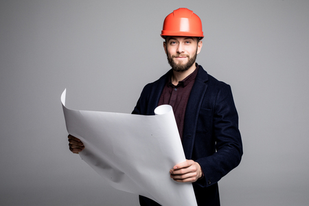 architect tools: Portrait of an architect builder studying layout plan of the rooms, serious civil engineer working with documents on construction site. Stock Photo
