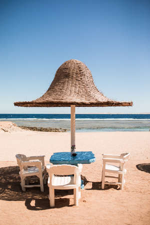 Vacation holidays. beach lounge chairs under tent on beach. Stock Photo