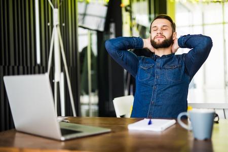 青年実業家のオフィスで彼の机でリラックス