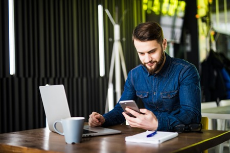 Young happy businessman smiling while reading his smartphone. Portrait of smiling business man reading message with smartphone in office. Man working at his desk at office. Banco de Imagens