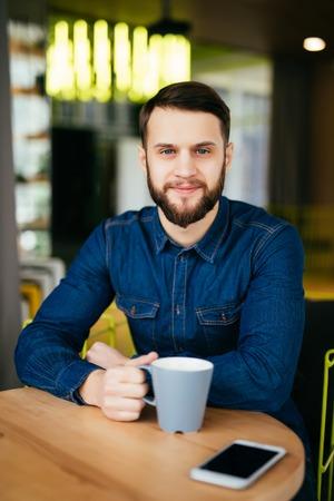 ハンサムな若者は彼の近くの店で敷設の携帯電話で、テーブルに座ってカフェで楽しむコーヒー