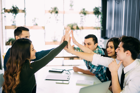 editors: Photo editors giving high-five in meeting room at creative office room