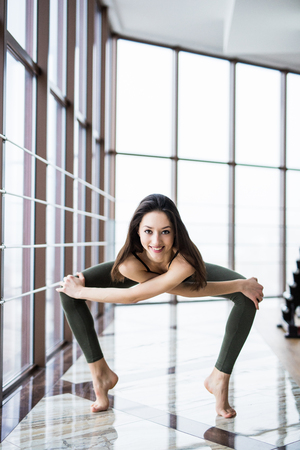 Beautiful yoga woman practice near window yoga room studio background. Yoga concept.