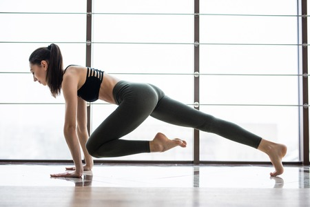 plank position: Working her core muscles. Full length of young beautiful woman in sportswear doing plank while standing in front of window at gym