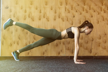 plank position: Perfect plank. Full-length side view of young beautiful woman in sportswear doing plank while standing in front of window at gym