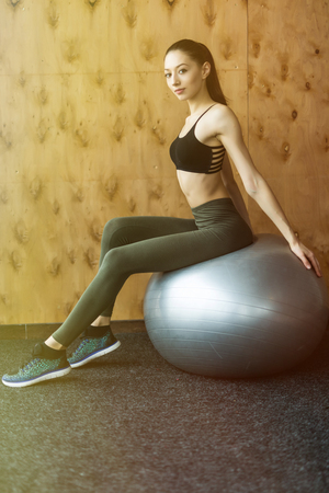 fitness, sport, training, gym concept - young woman doing exercise on fitness ball