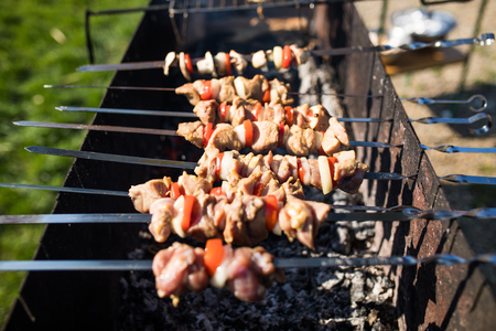 Grilling marinated shashlik on a grill. Shashlik is a form of Shish kebab popular in Eastern, Central Europe and other places. Shashlyk meaning skewered meat was originally made of lamb.