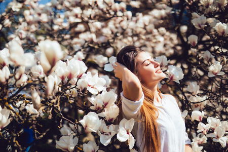 Outdoor portrait of a young beautiful woman near magnolia tree with flowers. Girl wearing stylish clothes. Stock Photo