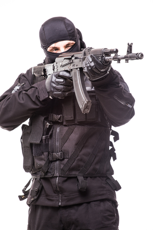 Armed terrorist in black mask and black uniform aiming with a gun.