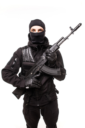 Portrait of dangerous bandit in black wearing balaclava and holding gun in hand on white Stock Photo