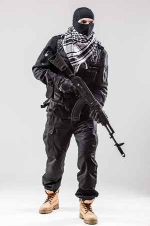 taliban: Terrorism concept: Terrorist holding a machine gun in his hands isolated over white