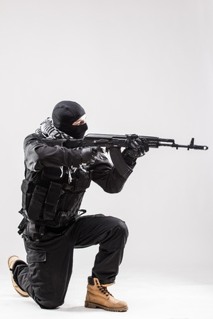 Terrorism concept: Terrorist holding a machine gun in his hands isolated over white