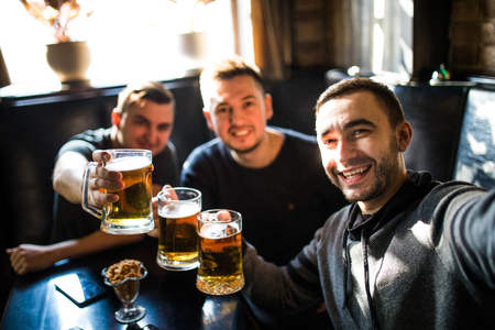 male friends drinking beer and taking selfie with smartphone at bar or pub