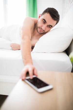 Young man in white atmosphere close the alarm off of his phone