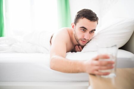 sleeping pills: Handsome man wake up in the morning and extend to drink a glass of water in bed Stock Photo