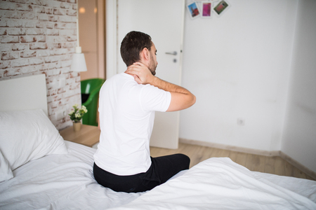 man suffering from neck ache in bed at home Stock Photo