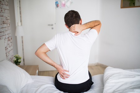Man suffering from back pain at home in the bedroom. Stockfoto