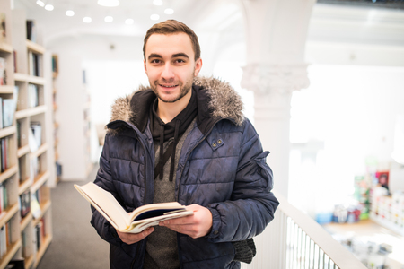 man reading a book in book store wearing in winter jacket