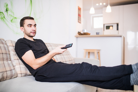 Man with remote control on sofa at home