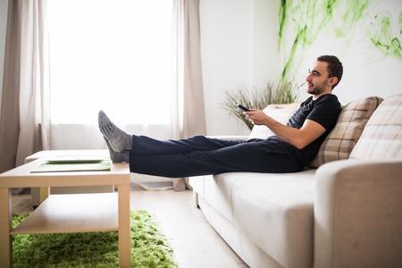 リビング ルームのソファに座ってリモコンを使用して若い男の背面図 写真素材