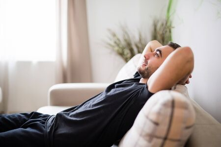 domicile: Smiling man lying and relaxing on the couch at home in the living room