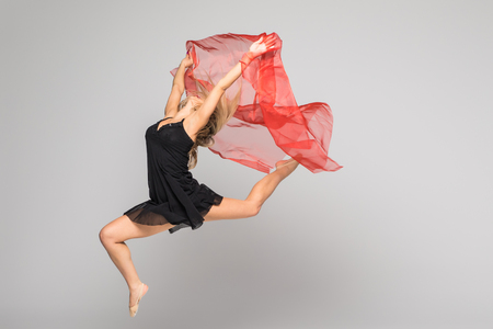 Beautiful dancer on aerial silk in studio on white background. Air acrobatic young women stunts isolated