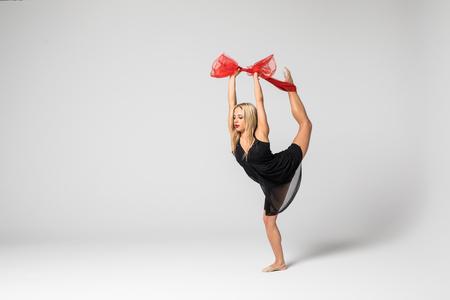Krásná tanečnice na leteckém hedvábí ve studiu na bílém pozadí. Vzduch akrobatické mladé ženy stunts izolované