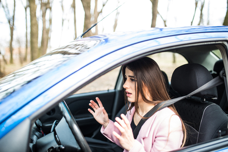Woman driver scared shocked before crash or accident hands out of wheel on road