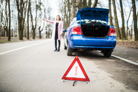 roadside stand: Woman putting a triangle on a road,car trouble