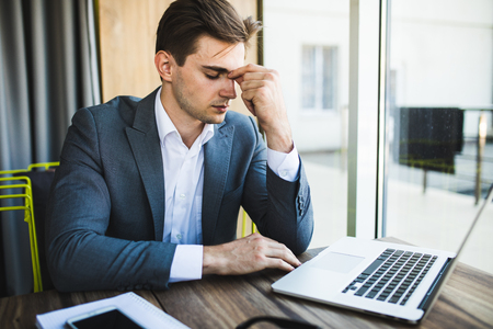 tired businessman: frustrated business man working on laptop computer at office