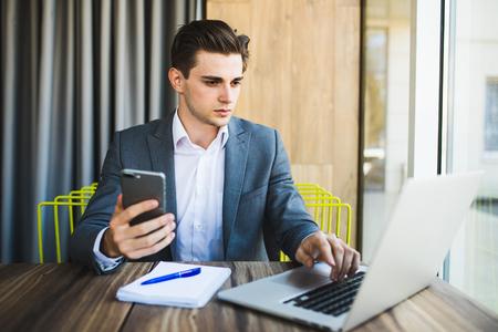 彼のスマート フォンを読んで笑って若い幸せな実業家。オフィスでスマート フォン ビジネス男読書メッセージを笑顔の肖像画。 写真素材
