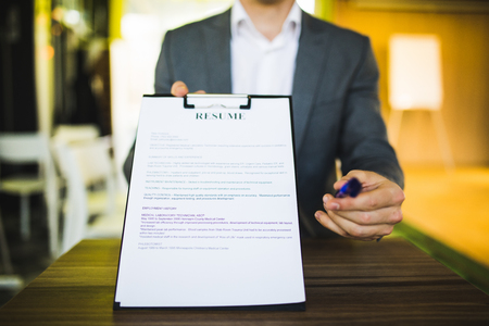 Young businessman submitting resume to employer to review - job application and interview concepts Stock Photo