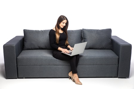 horozontal: happy brunette woman sitting on sofa with laptop