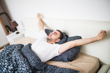 eyesclosed: Yawning and stretching man waking in bed