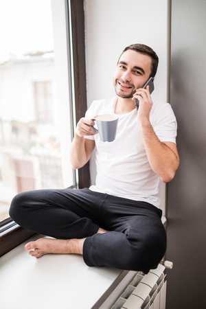 Handsome man sitting on windowsill and calling on phone Stock Photo