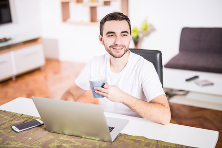 Handsome man drinking coffee while working with laptop in kitchen Stock Photo