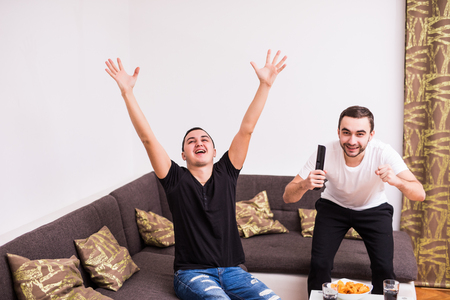 couple on couch: buddies watching football match on tv at home
